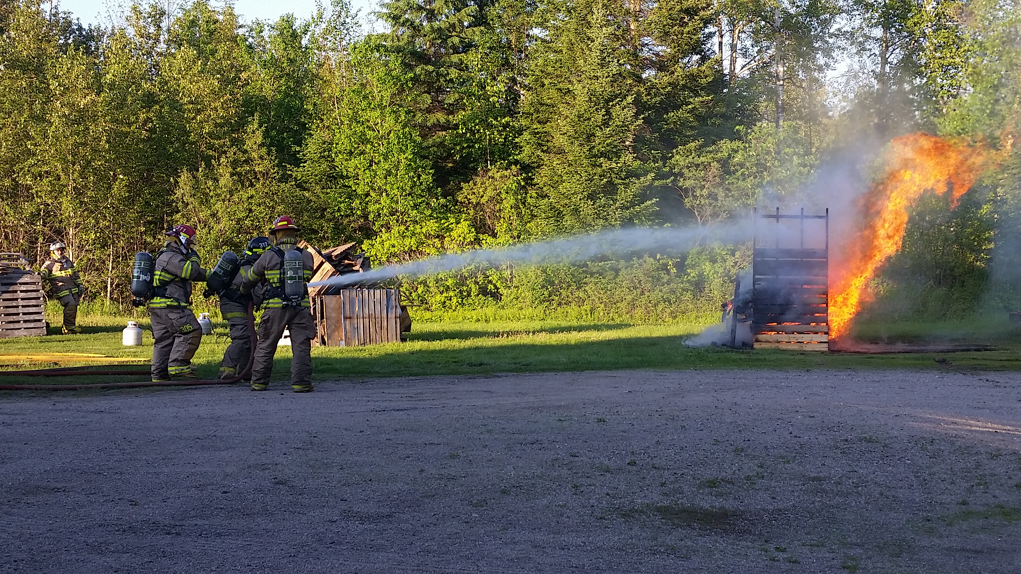 firefighters spraying water onto a fire