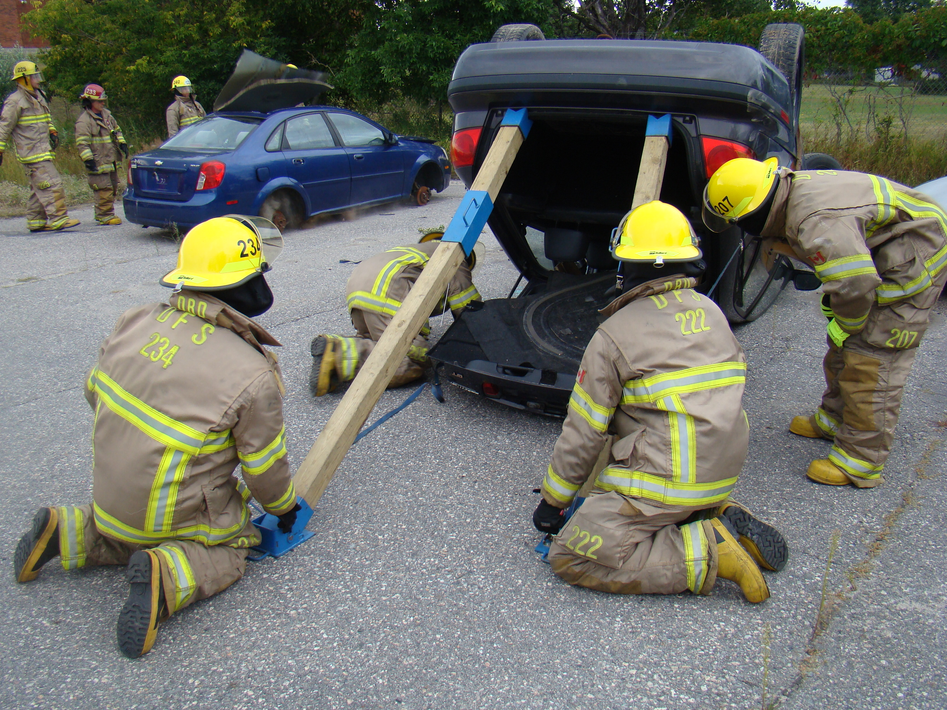 Photo of firefighters bracing an overturned vehicle as part of vehicle extrication training