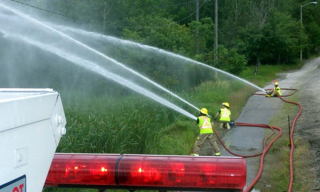 firefighters spraying water from fire hoses