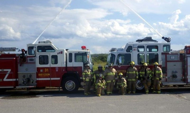 group of firefighters in front of two fire trucks