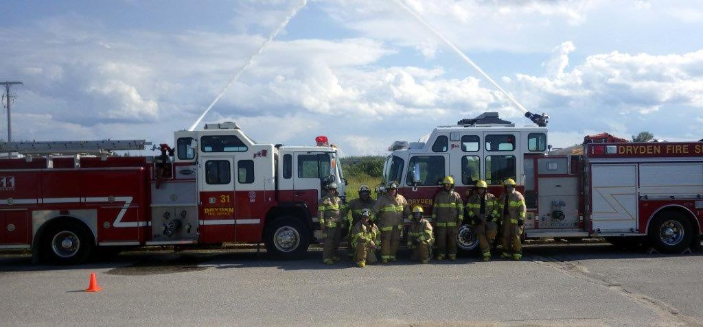 Photo of group of firefighters at pumper operations training, fire trucks in the background