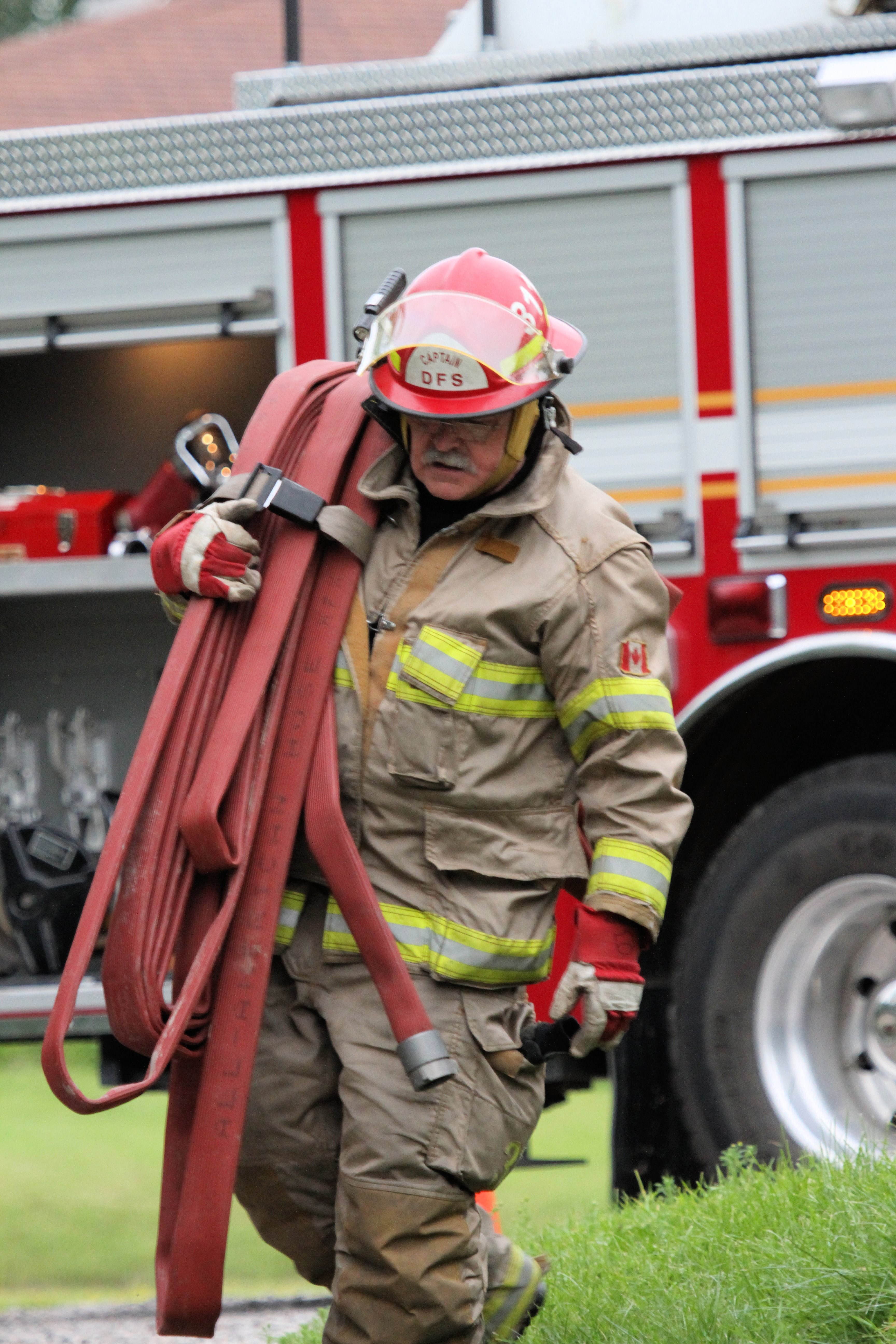 firefighter carrying fire hose
