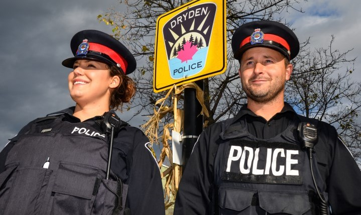 officers posing in front of police sign